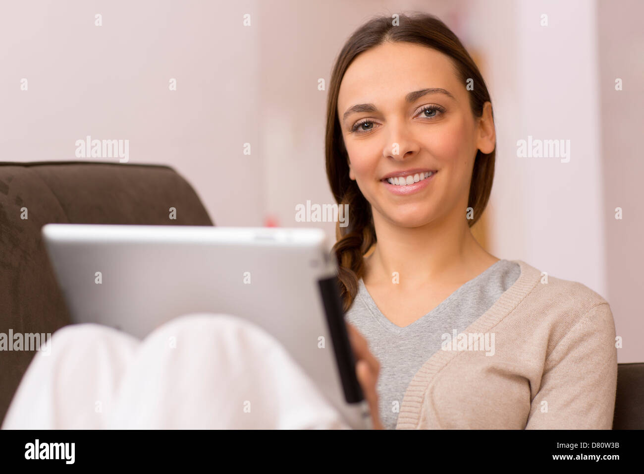 female consults email on pad, she look at the camera - Stock Image