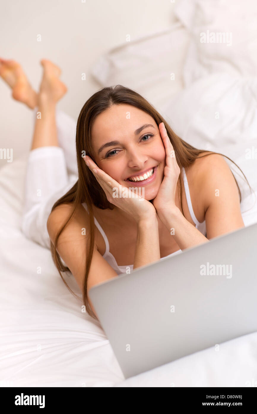 Attractive young woman at home working on laptop in bedroom - Stock Image