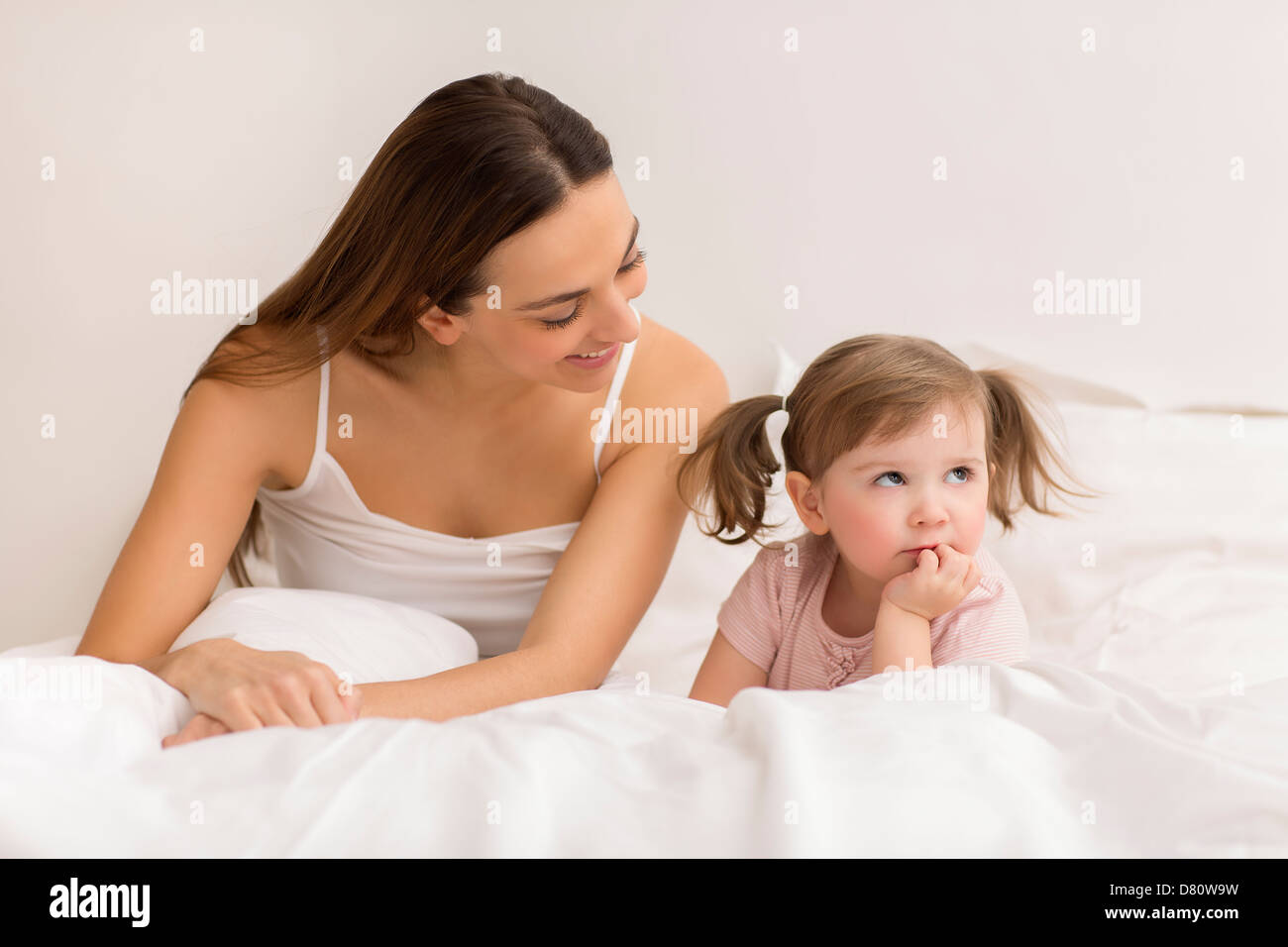 Dispute between a child and her mom in white bedroom - Stock Image