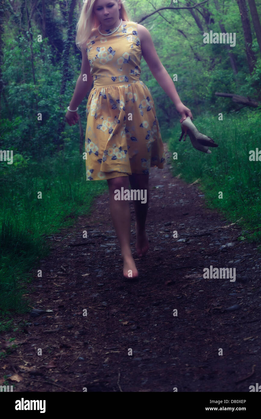 a girl in a yellow dress is running through the woods - Stock Image