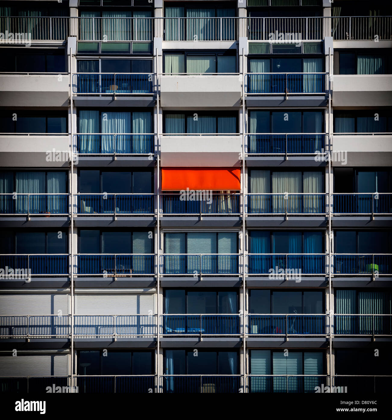 an apartment house with one red awning - Stock Image