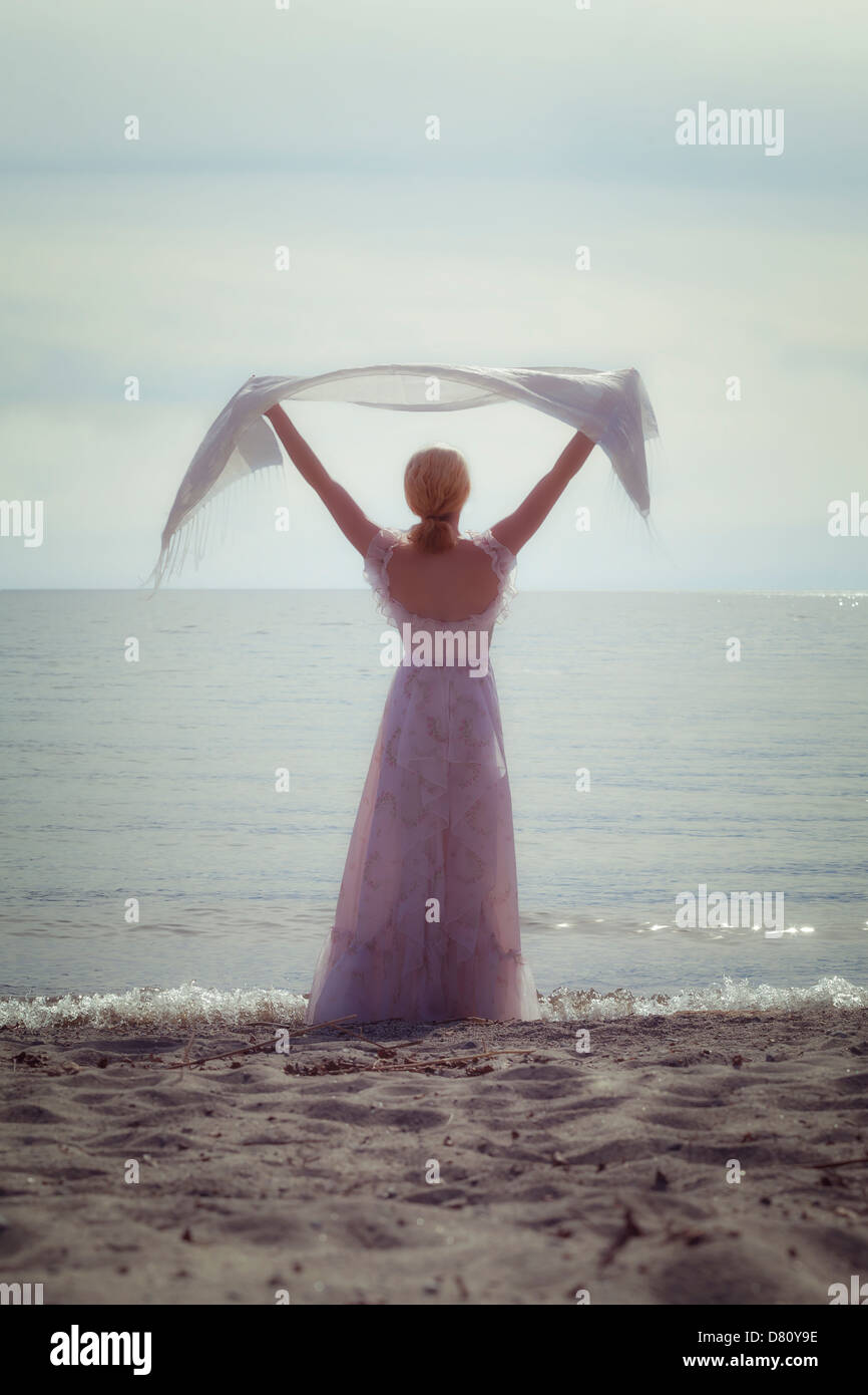 a woman at the beach with a white shawl - Stock Image