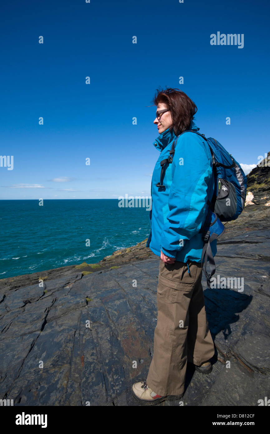 A female hiker taking in the view of the coastline at near Boscastle in north Cornwall, England, UK - Stock Image
