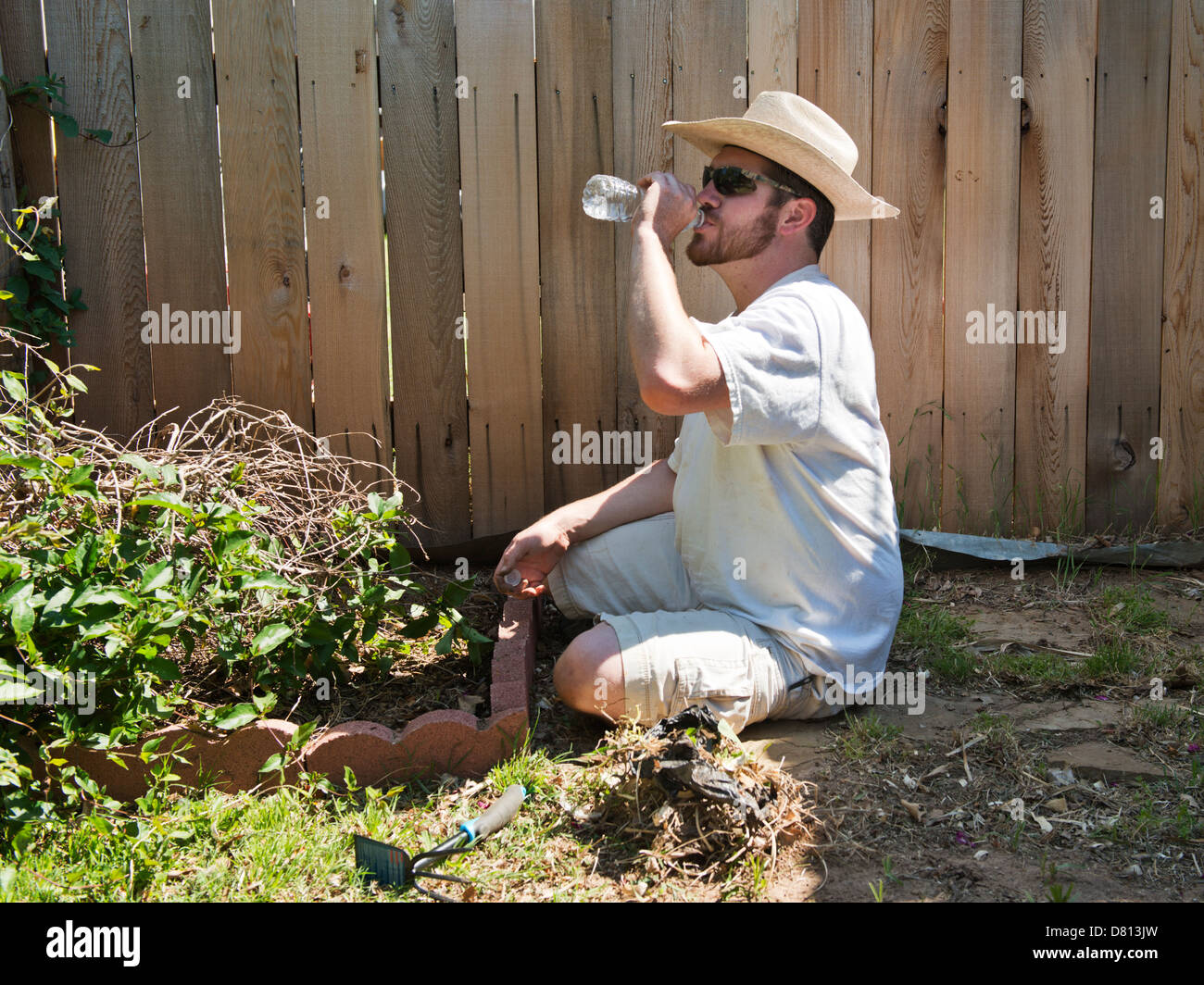 A Caucasian man, 27 years old, drinks bottled water while gardening ...