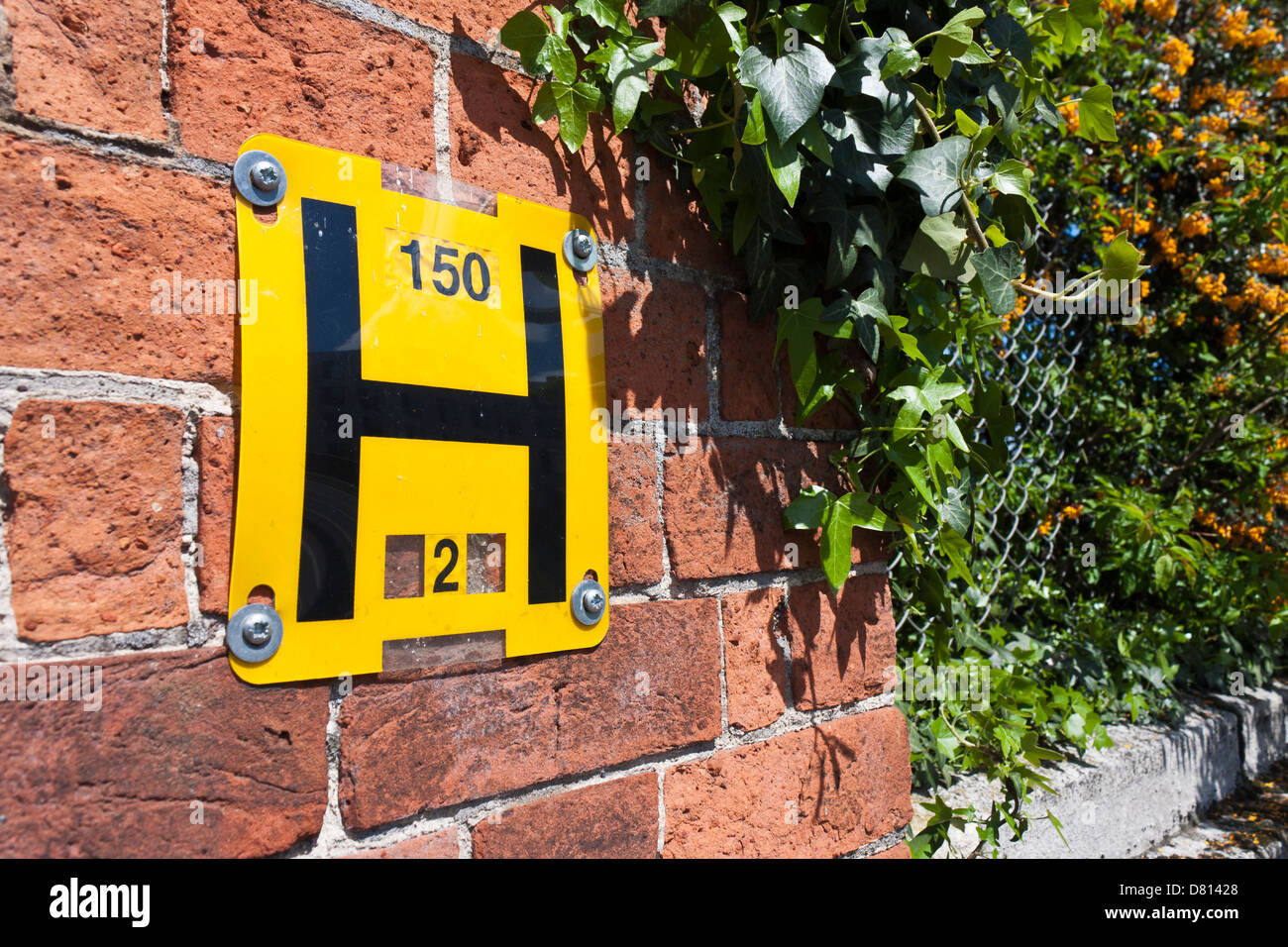 Metric water hydrant sign on wall at roadside. - Stock Image