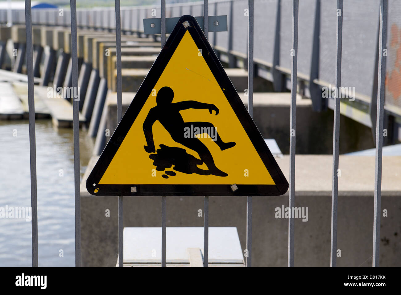 A warning sign indicating a slippery surface near the sluice gates of Cardiff Bay, UK. - Stock Image