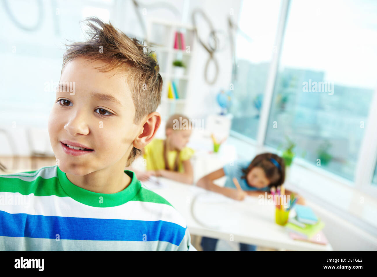Portrait of handsome learner doing sums with schoolmates on background - Stock Image