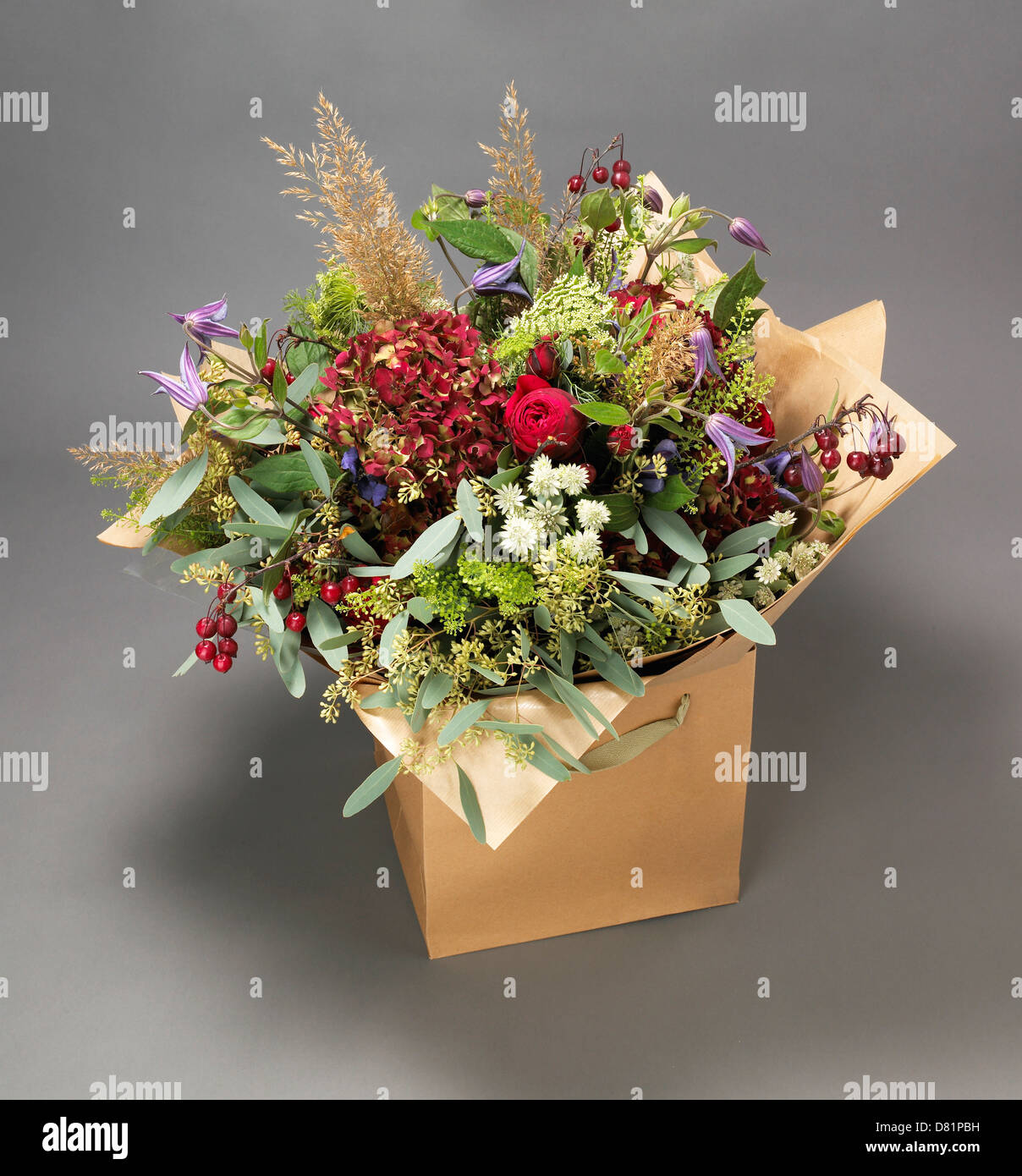 Large bunch of flowers including roses and meadow flowers displayed in a cardboard box on a grey background - Stock Image