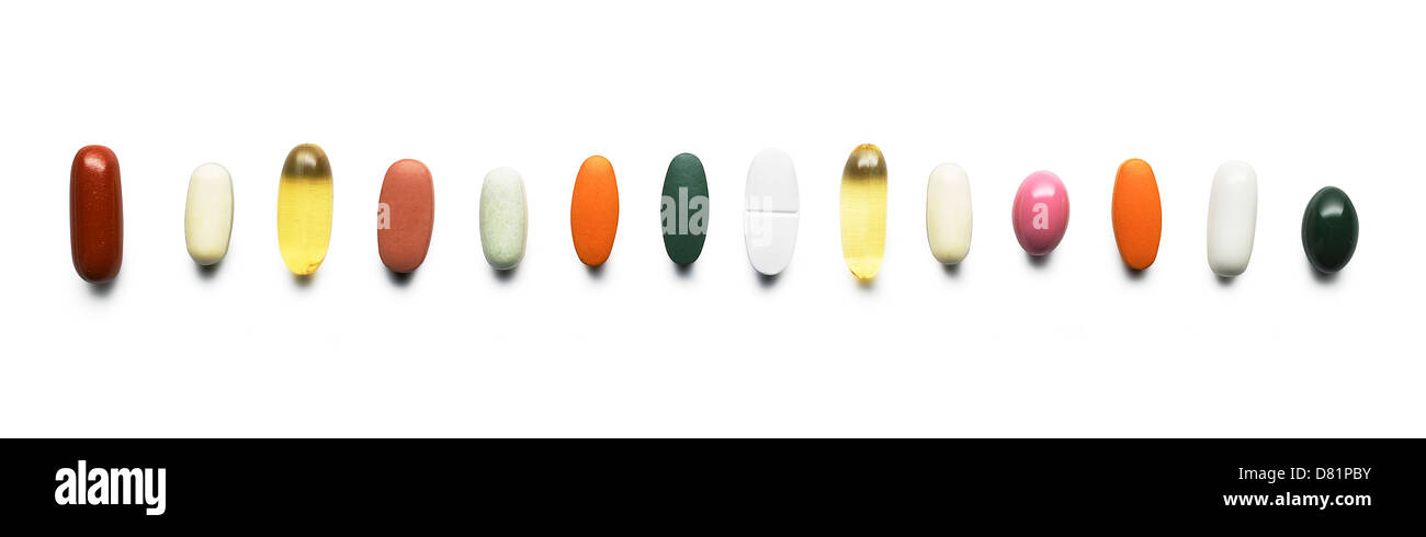 row of coloured vitamins and pills cut out onto a white background - Stock Image