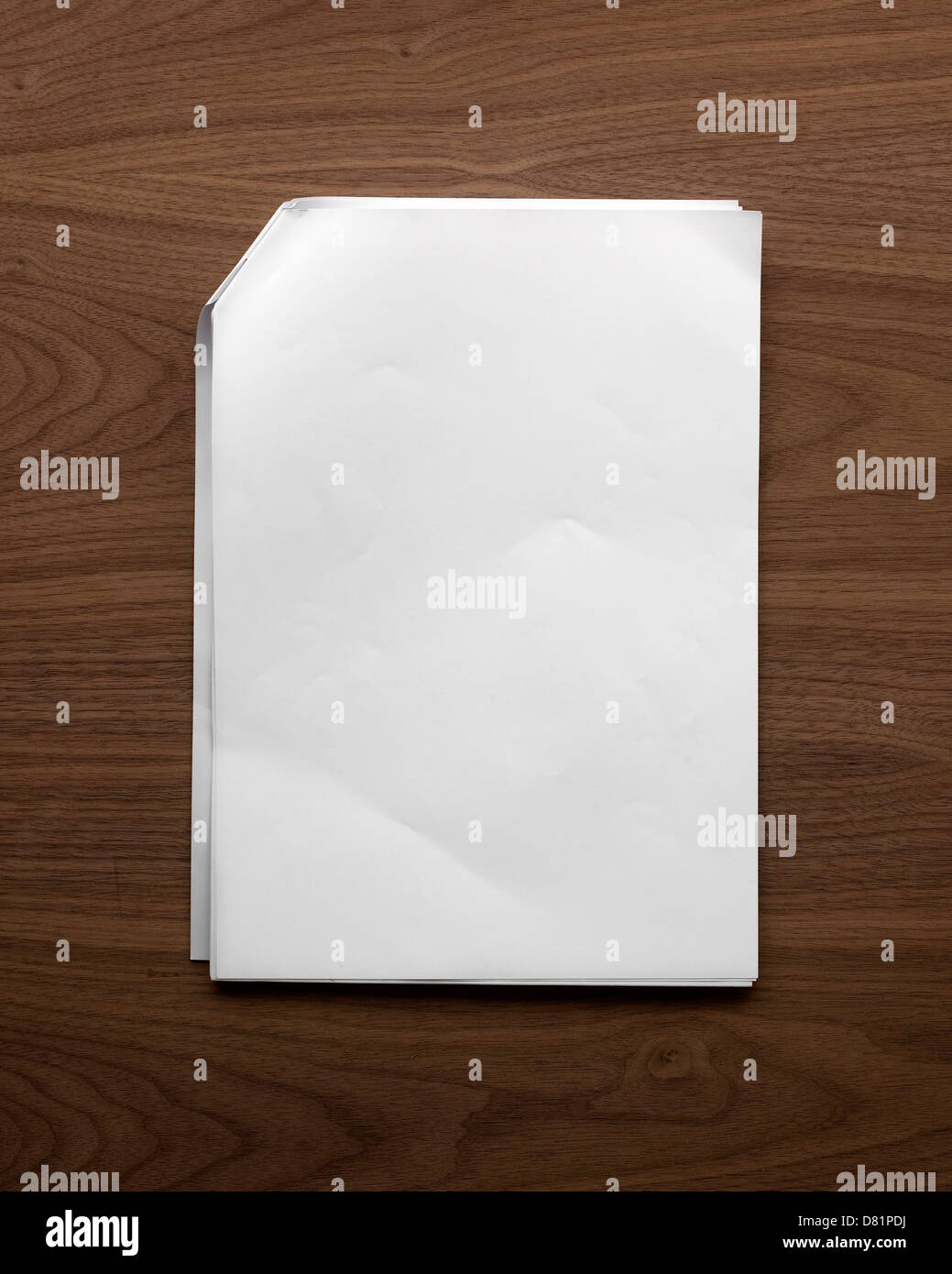 sheets of plain white paper stapled at the corner and folded over lying flat on a wooden table or desk shot from - Stock Image
