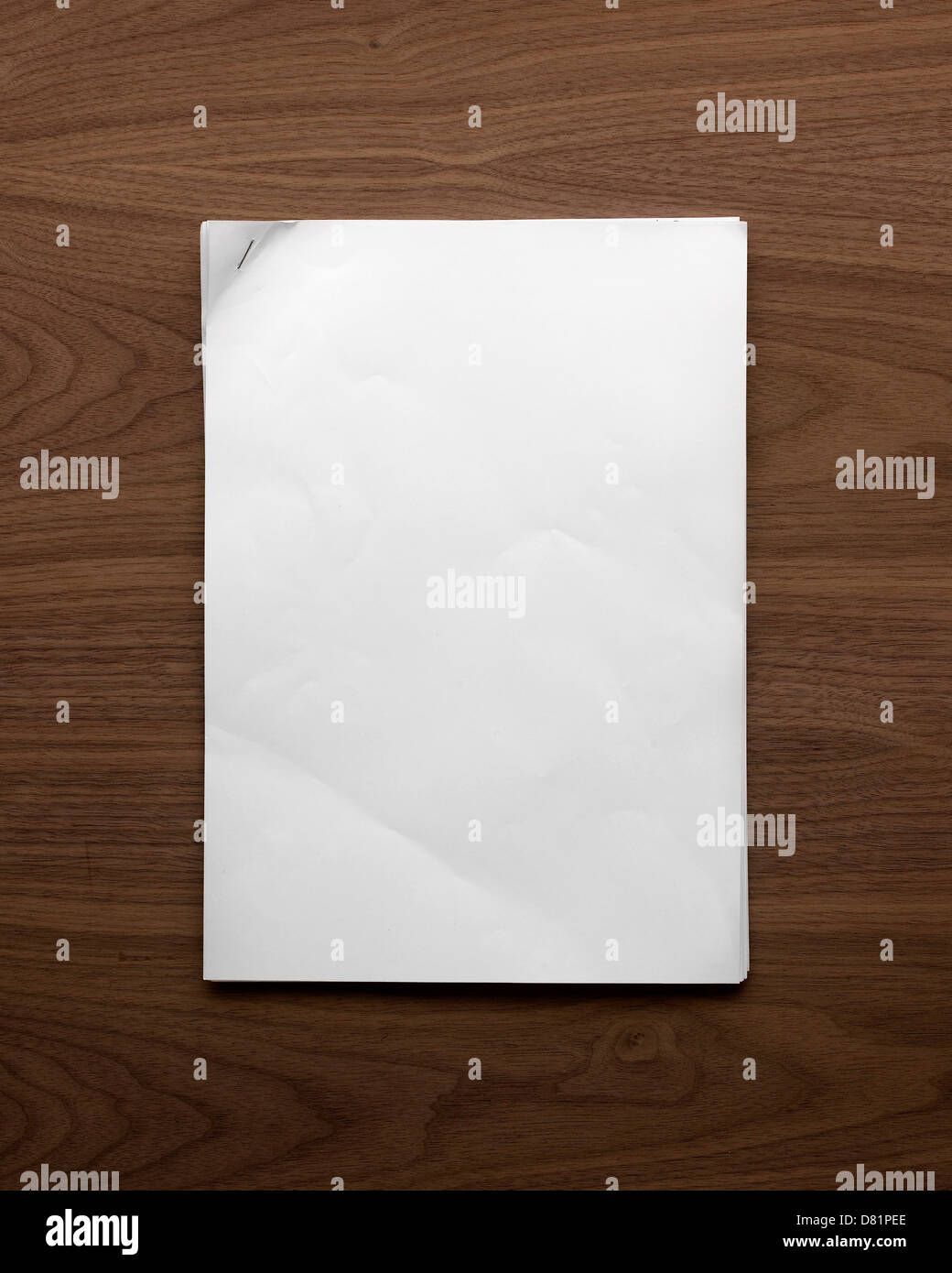 plain sheet of A4 paper with a stapled corner lying flat on a wooden table shot from above - Stock Image