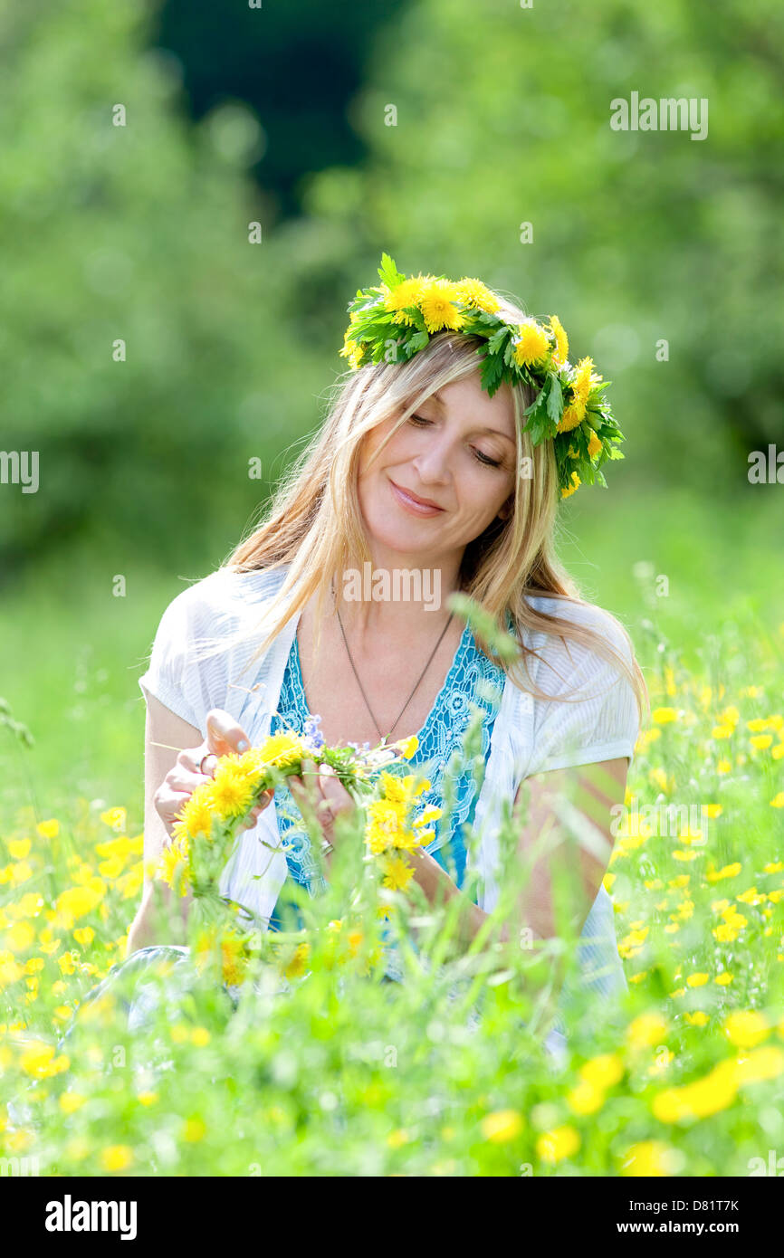 woman with flower wreath siting in a spring meadow - Stock Image