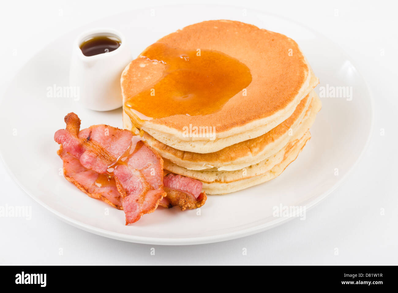 Pancakes, bacon and maple syrup on a white background. - Stock Image