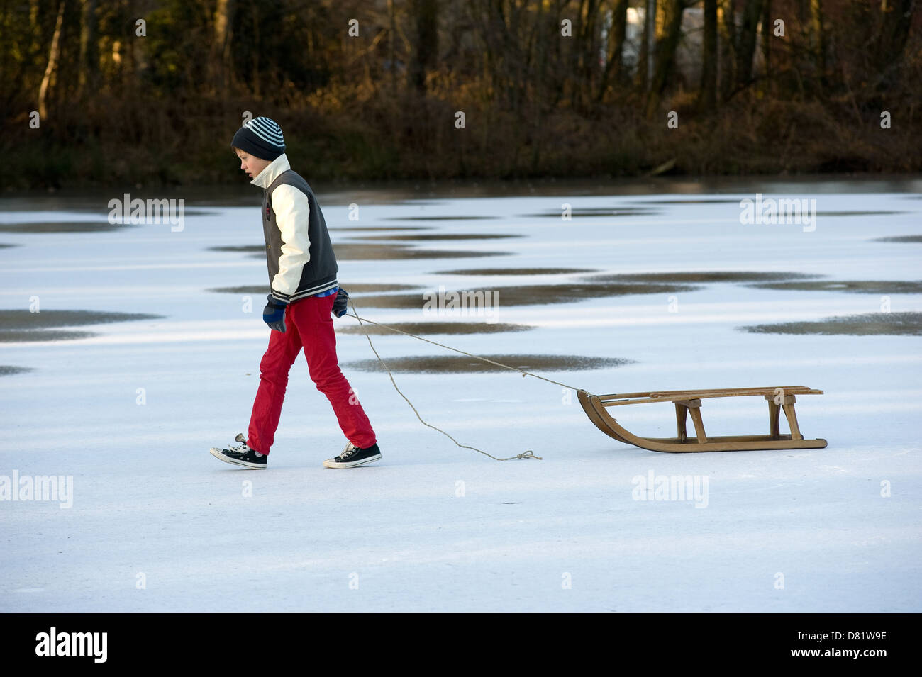 A boy is walking on a frozen pond with his sledge - Stock Image