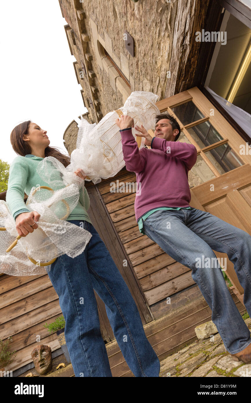 Man and woman carrying wrapped item into building - Stock Image