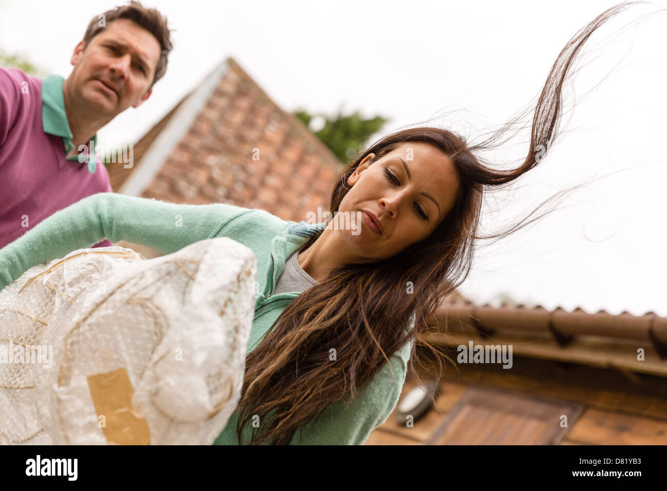 Man and woman carrying wrapped item - Stock Image