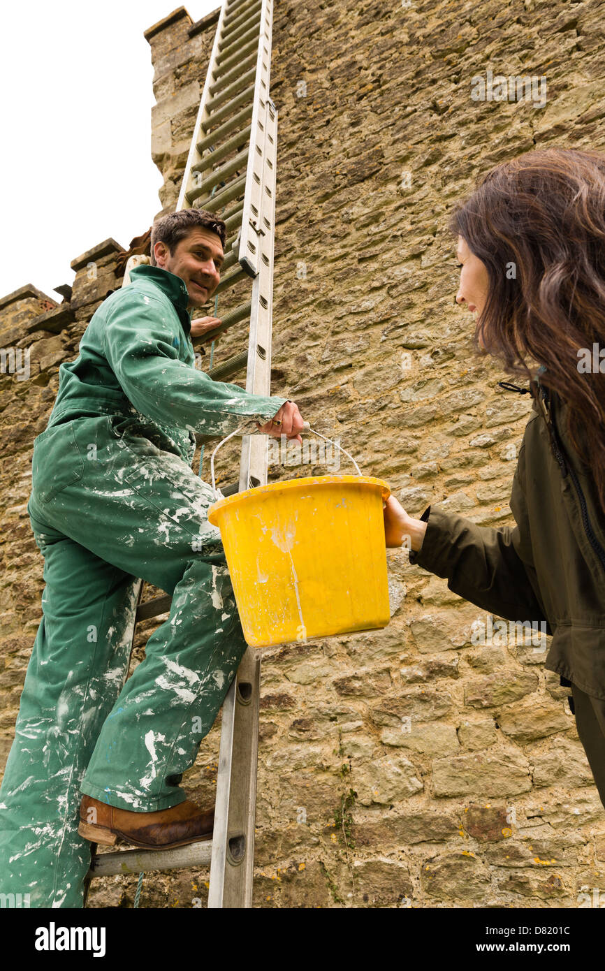 Woman passing yellow bucket to man on ladder - Stock Image