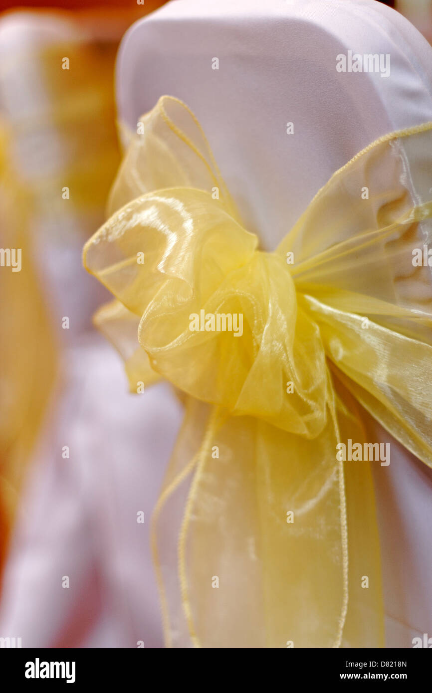 yellow ribbon tied into a bow over white chair cover stock photo