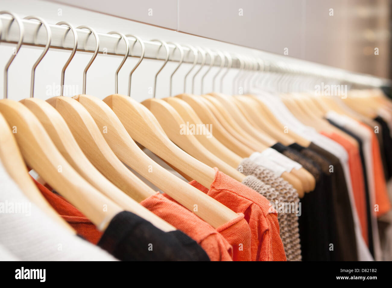 Clothes hang on a shelf in a designer clothes store in Melbourne, Australia - Stock Image
