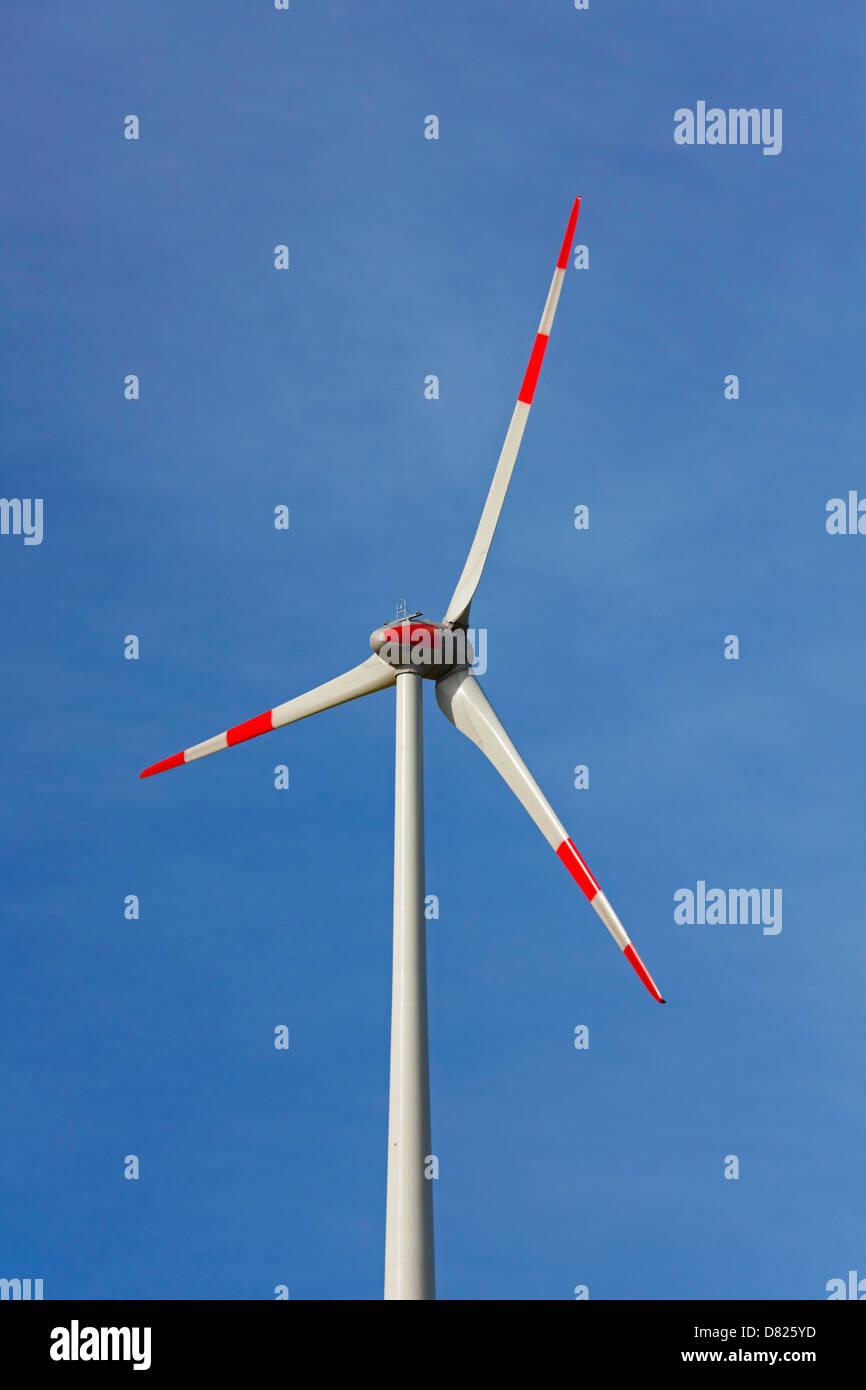 Wind turbine, renewable energy resource against blue sky - Stock Image