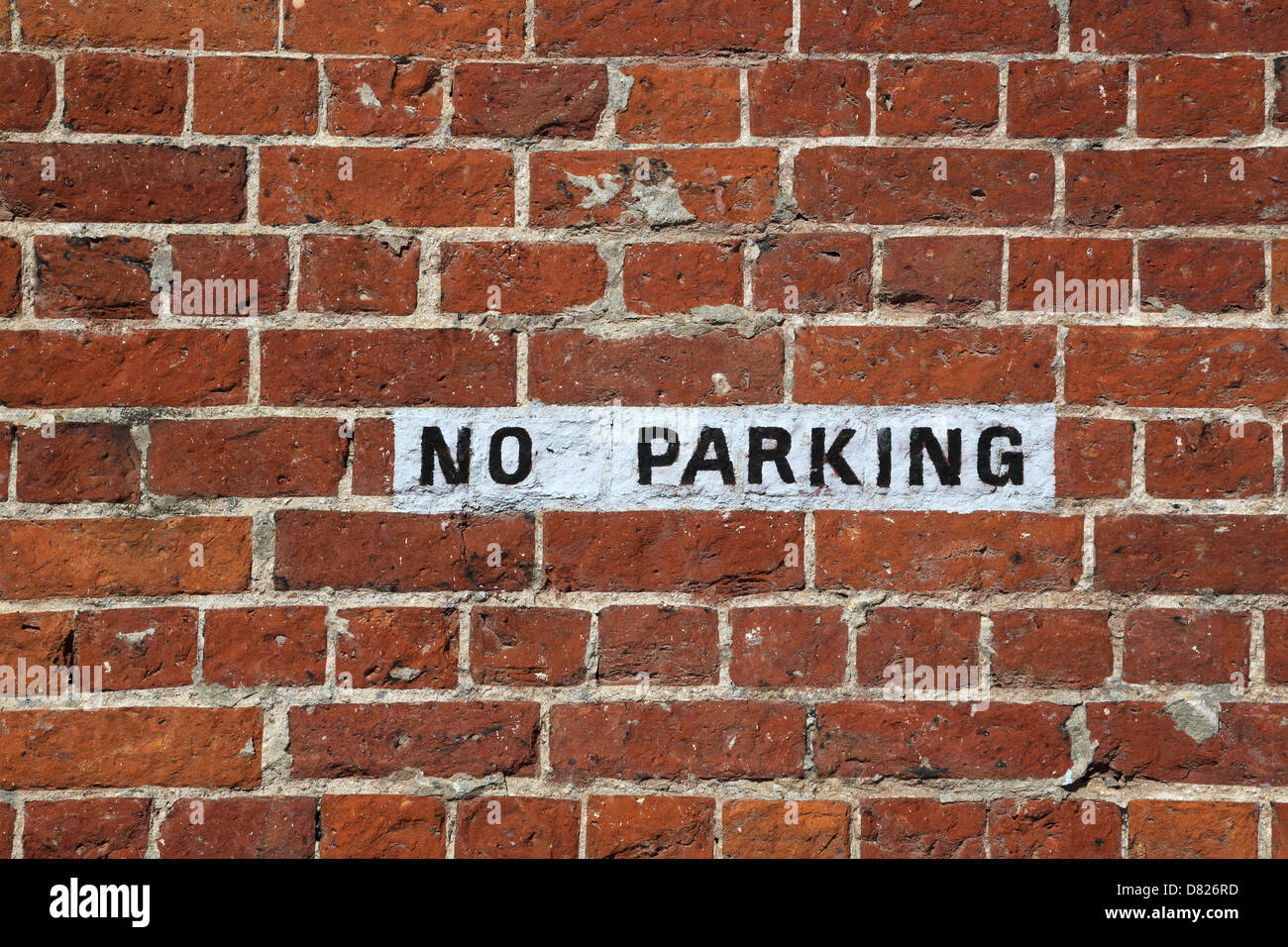 no parking sign painted on a brick wall - Stock Image
