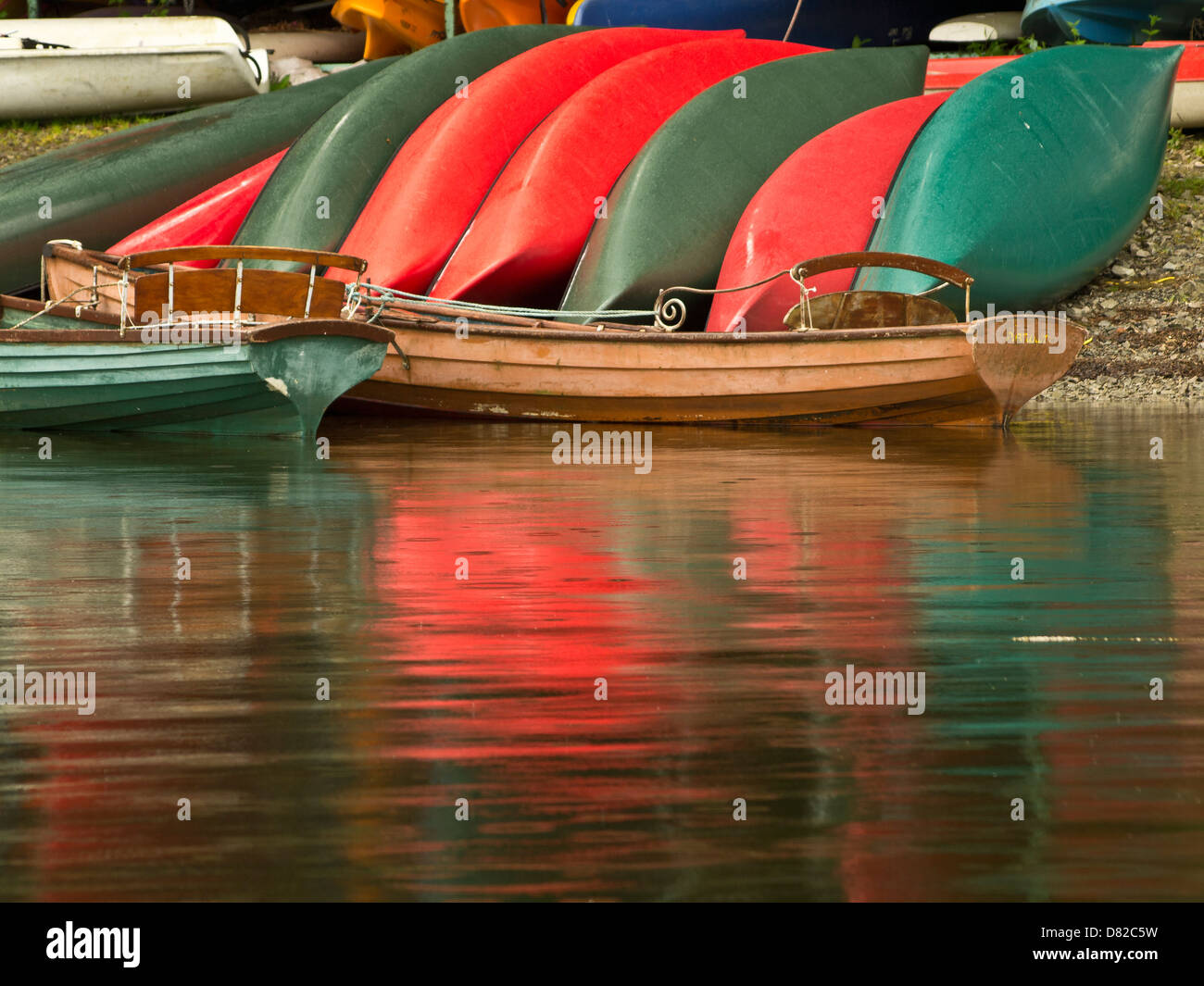 Red and green colorful bright boats at the shore of the lake, Nicol End, Lake District, Cumbria, UK - Stock Image