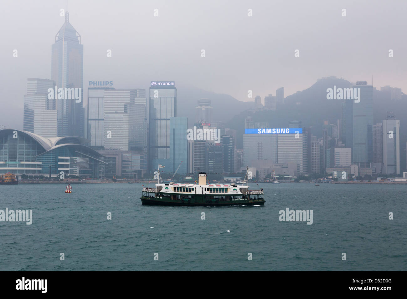 Star ferry crossing the Victoria Harbour in Hong Kong on a hazy day from Kowloon to Wan Chai Stock Photo