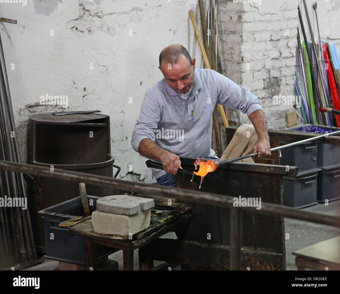 A man blowing a glass animal in a glass factory Murano Venice Italy - Stock Image