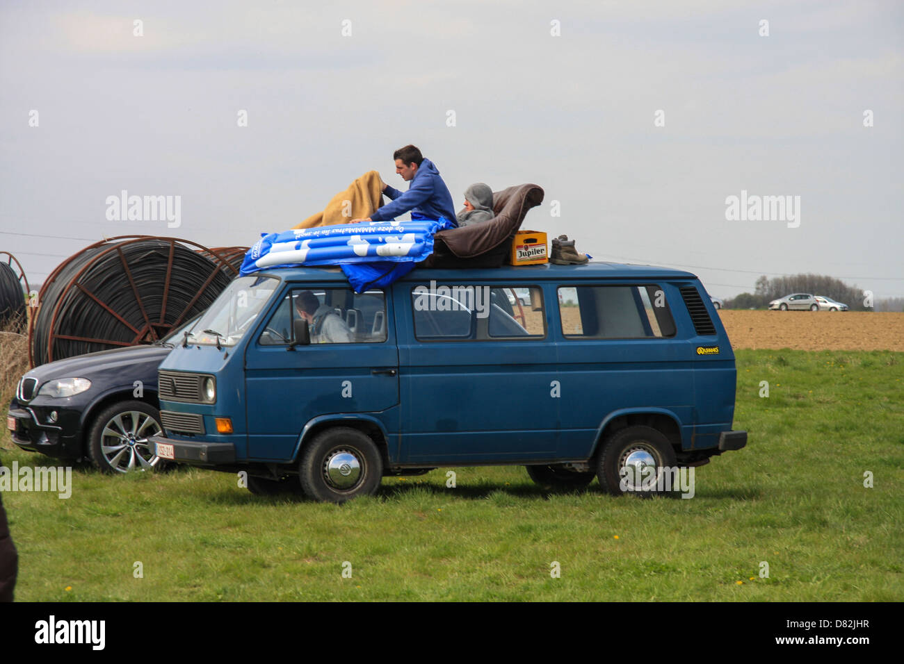 Paris - Roubaix crazy spectators sitting on the roof of their car, waiting for the race. - Stock Image