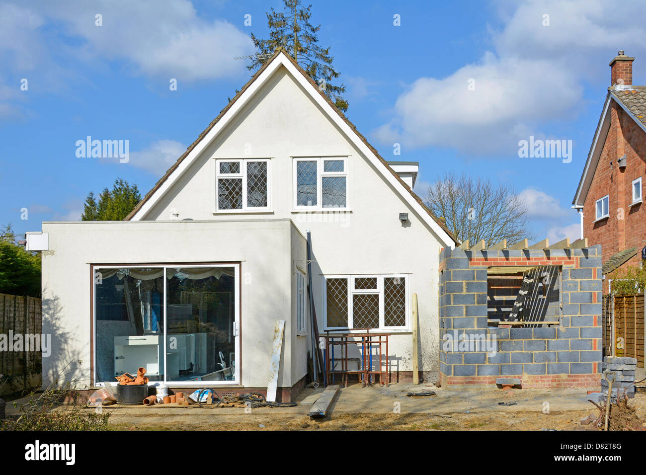 Building work to side of detached house to add two storey bedroom & kitchen extension seen from back garden - Stock Image