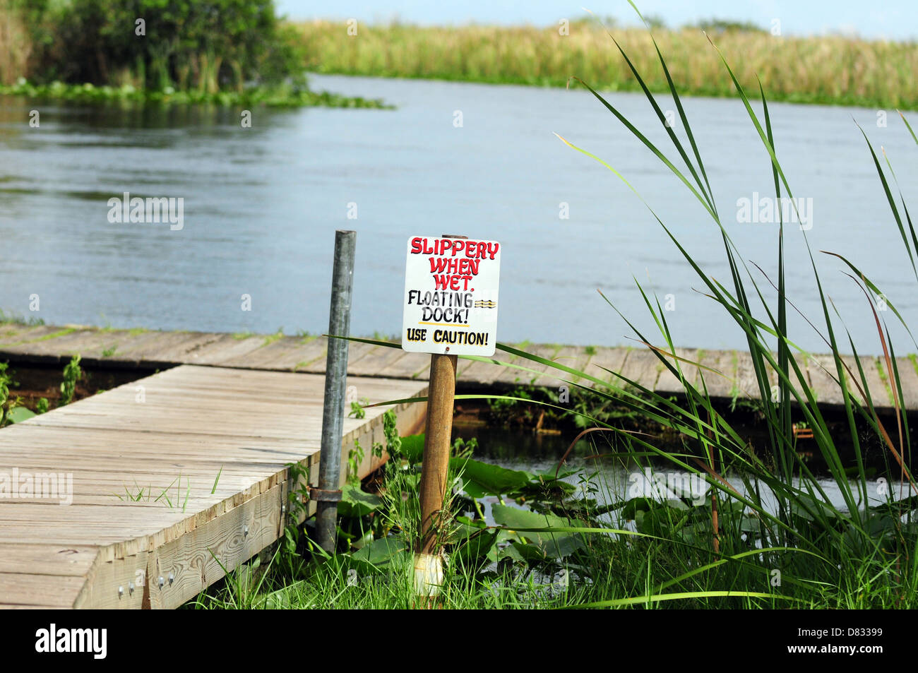 Slippery When Wet sign at floating dock near lake Stock Photo