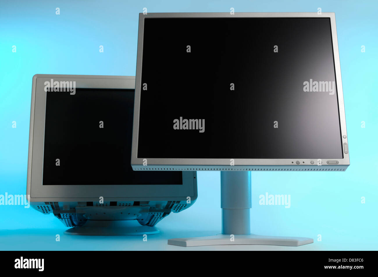 New LCD display and an old CRT monitor behind it. Technology, computers and electronics concept. - Stock Image