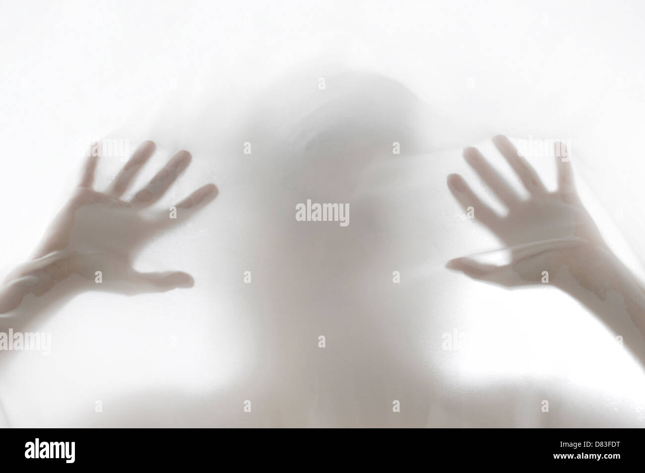 Mysterious woman silhouette behind white hazy fabric - Stock Image