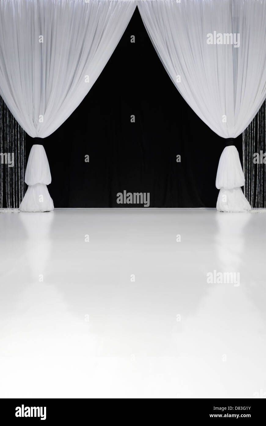 White stage curtains over black curtains in the background - Stock Image