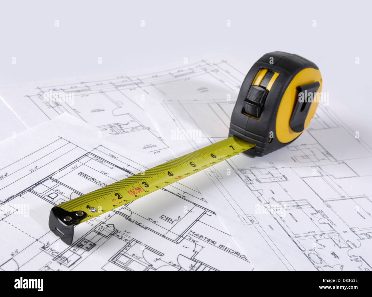 Tape measure on construction plans of a house - Stock Image