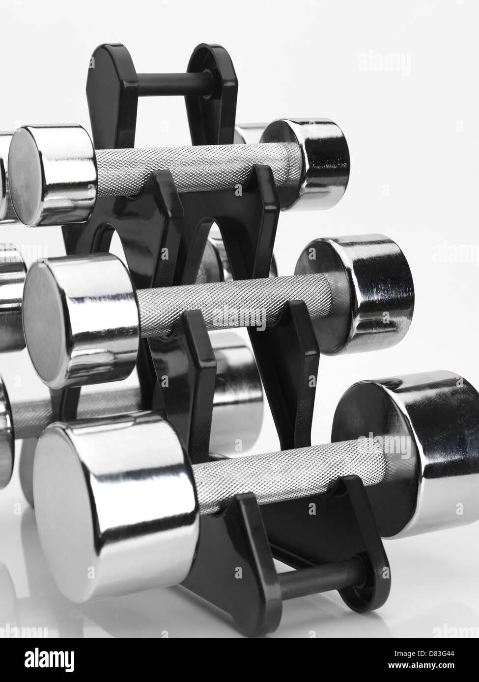 Rack with a set of shiny chrome dumbbells isolated on white background - Stock Image