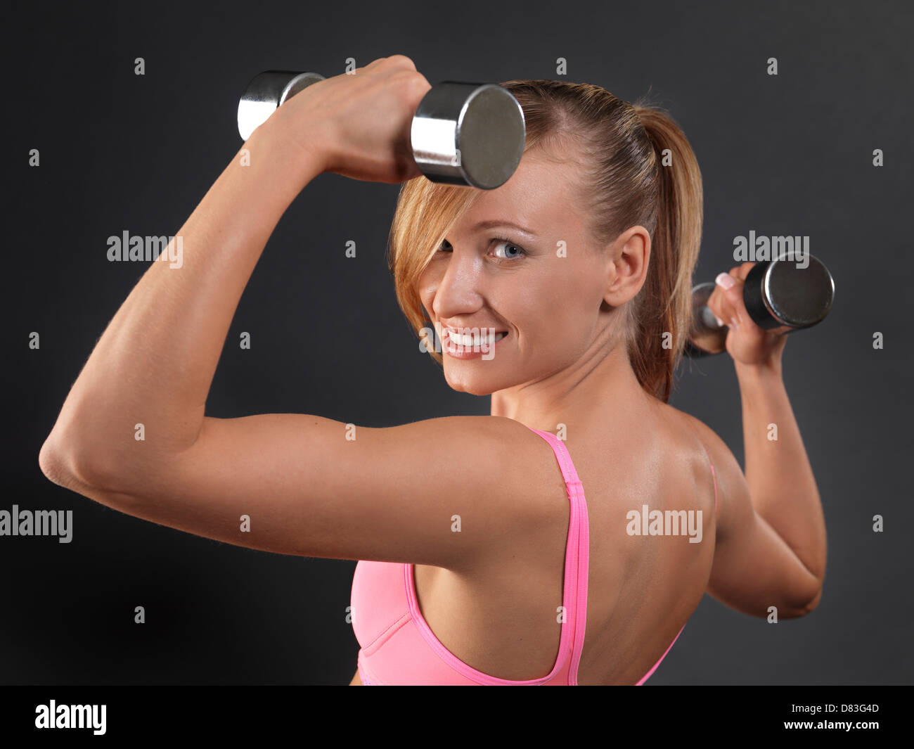 Portrait of a young smiling fitness woman exercising with weights - Stock Image
