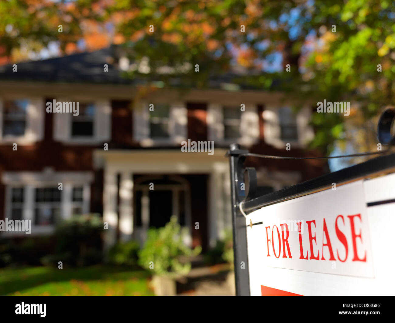 For lease sign in front of a large house in fall. Toronto, Ontario, Canada. - Stock Image
