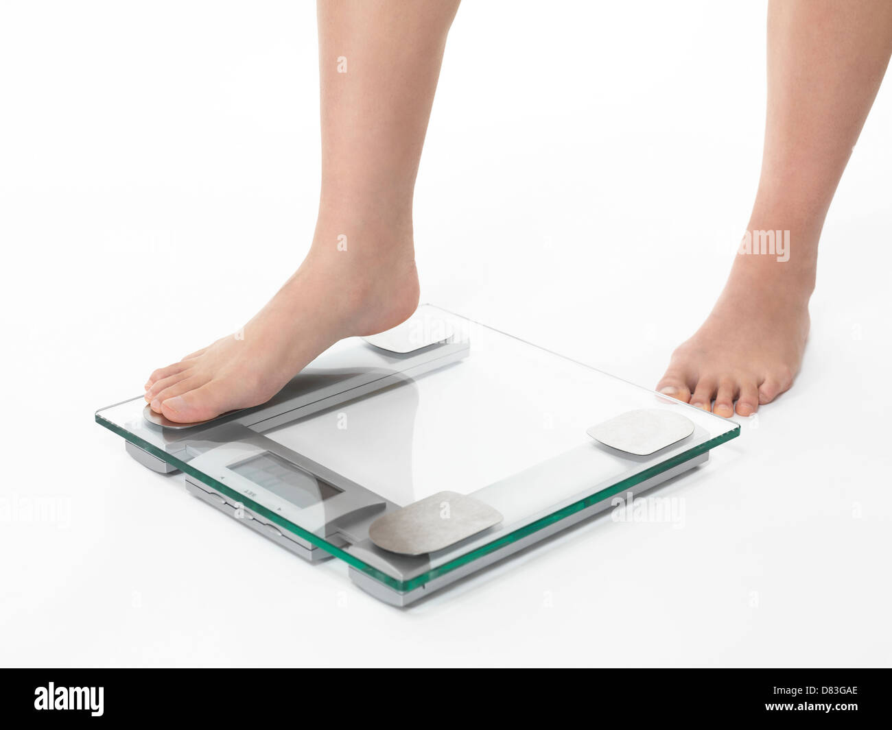 Closeup of woman legs stepping on weight scale. Isolated on white background - Stock Image