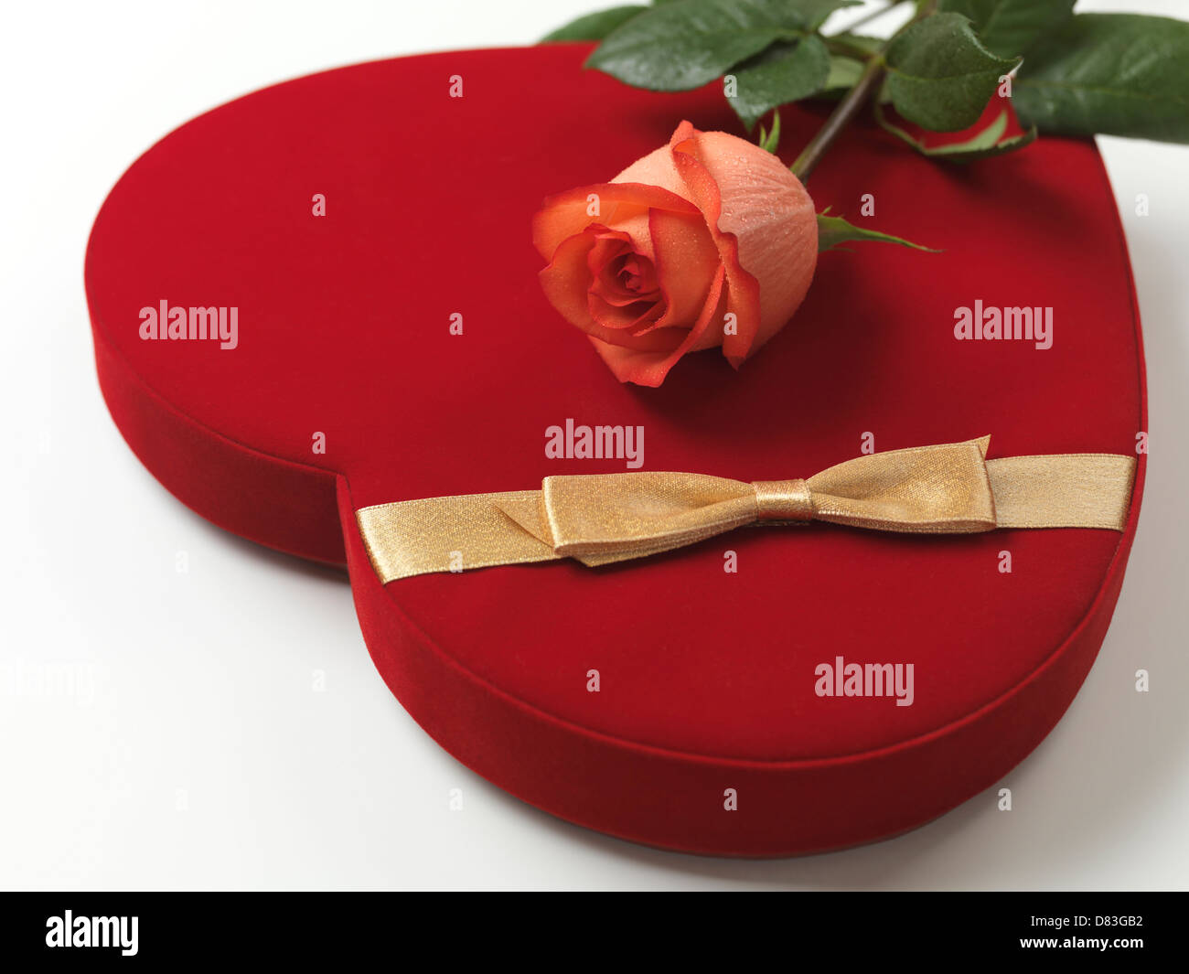 Red heart-shaped gift box and a pink rose Stock Photo