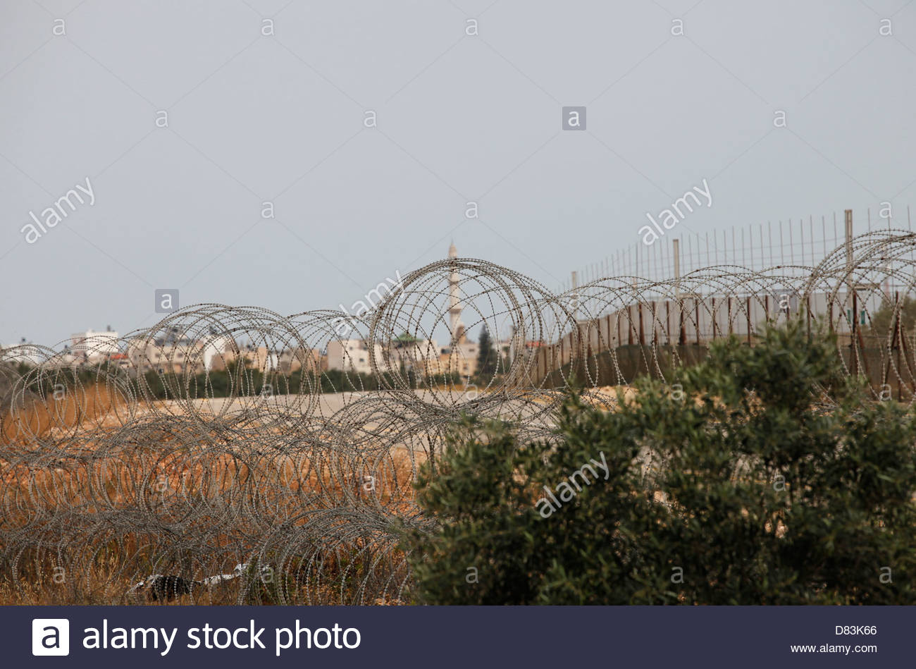 A Palestinian village is seen through barbed wires surrounding the religious Jewish settlement Modi'in Illit - Stock Image