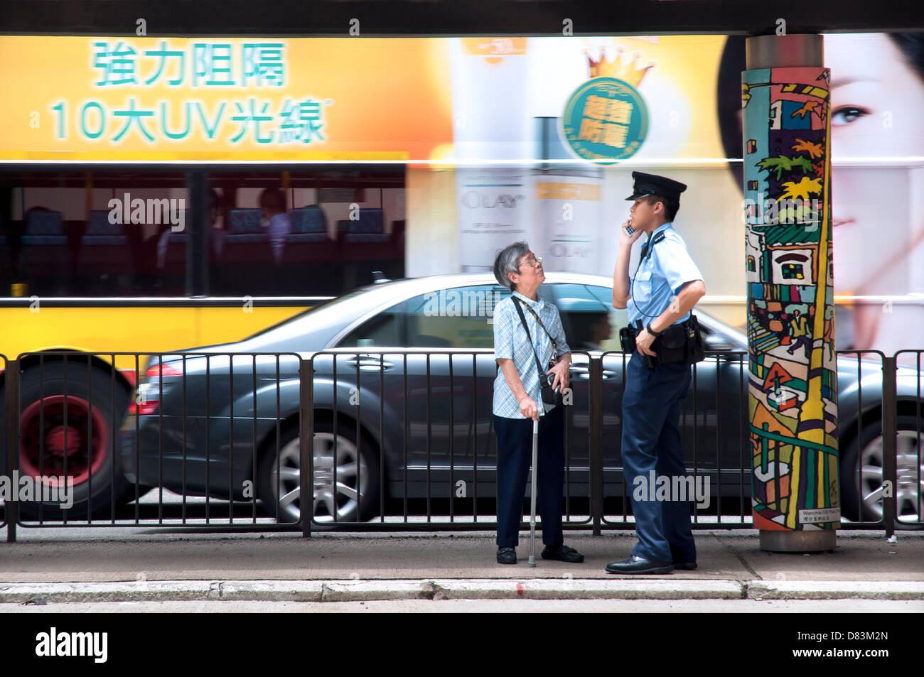 Hong Kong policeman helps an old lady on Hennessey Road, Wanchai, Hong Kong - Stock Image
