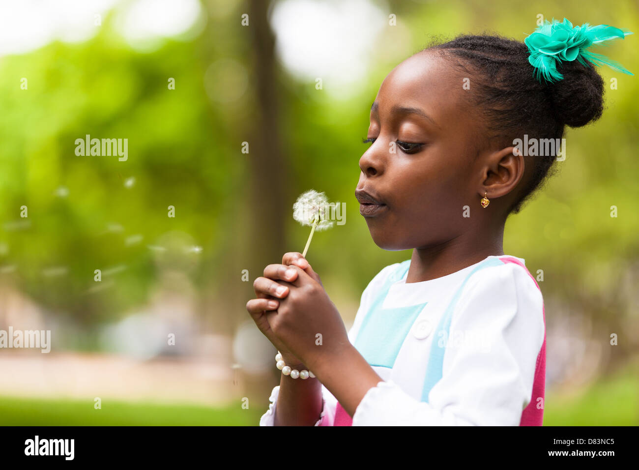 Outdoor portrait of a cute young black girl blowing a dandelion flower - African people - Stock Image