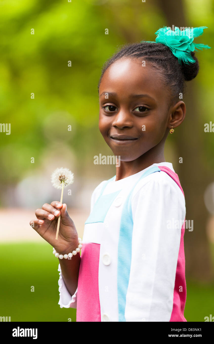 Outdoor portrait of a cute young black girl holding a dandelion flower - African people - Stock Image