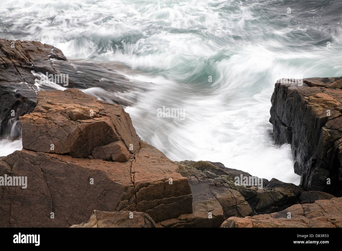 Waves crash along the rocky Maine coastline in Acadia National Park. - Stock Image