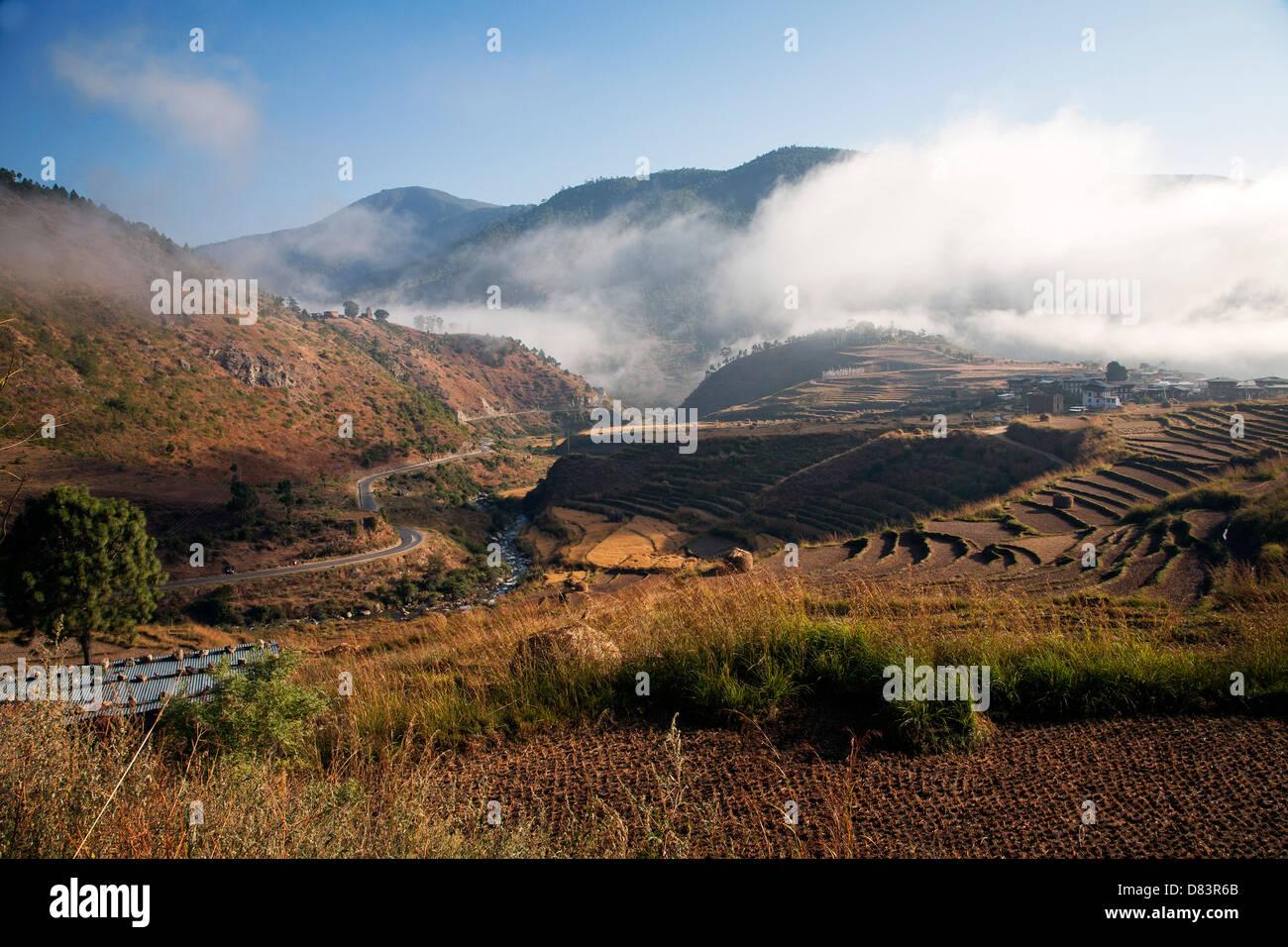 Morning fog burns of above the Punakha valley. Bhutan. - Stock Image
