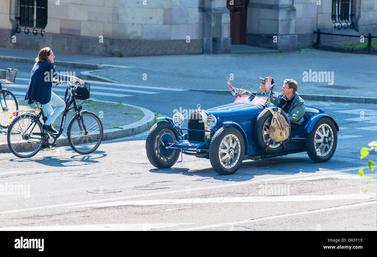 2 men driving a blue convertible Bugatti French vintage car waving female biker Strasbourg Alsace France Europe Stock Photo