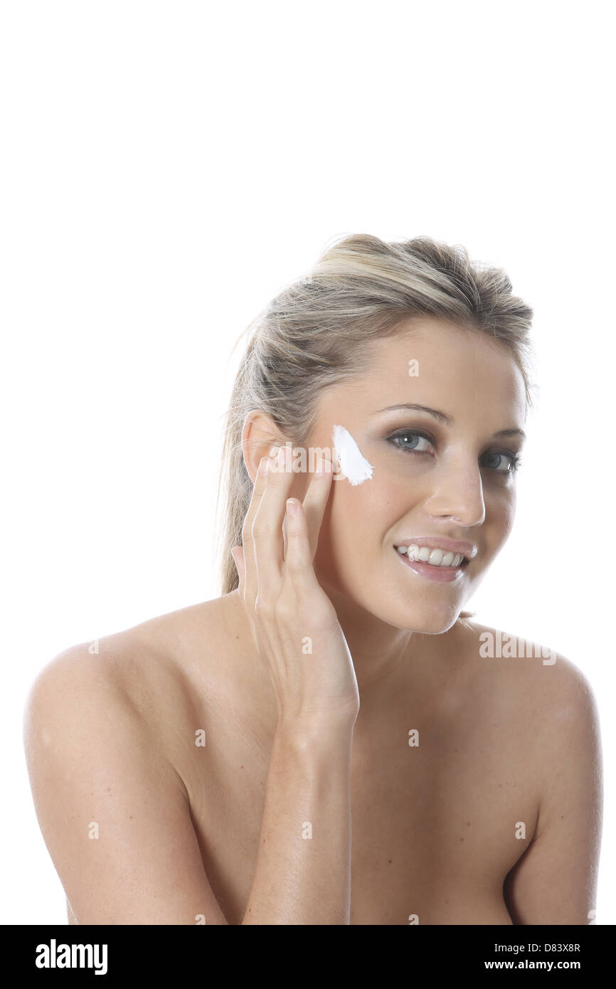 Model Released. Young Woman Applying Cream - Stock Image