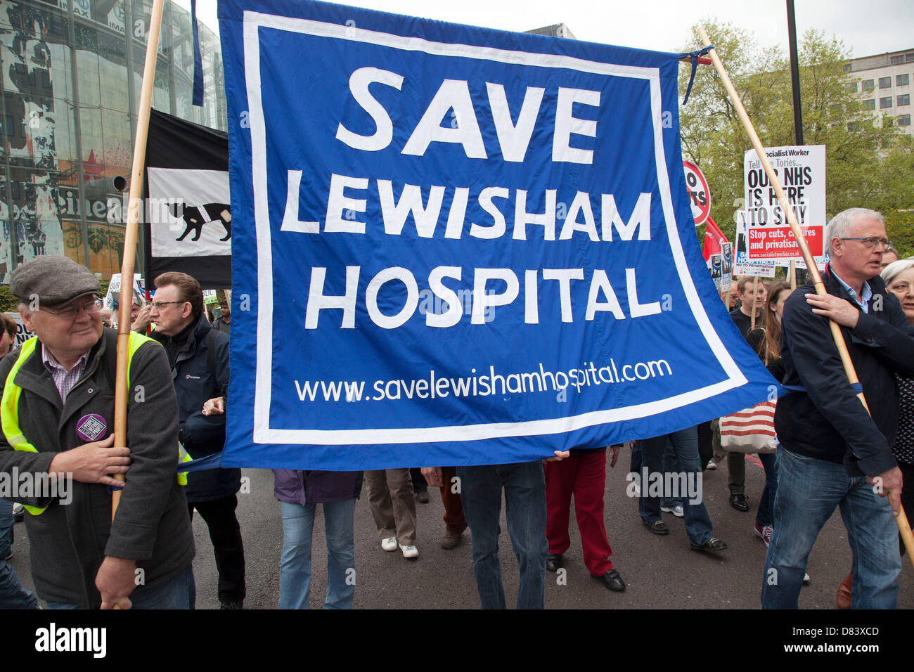 Protestors march in a demonstration against NHS reform and proposed funding cuts for services within the National - Stock Image