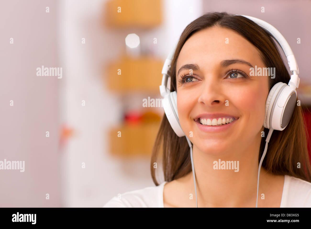 Pretty female with white headphones on head - Stock Image